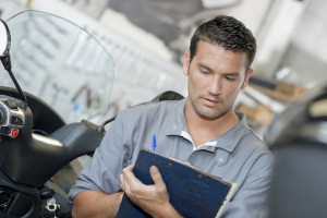 77138644 - mechanic making notes on clipboard